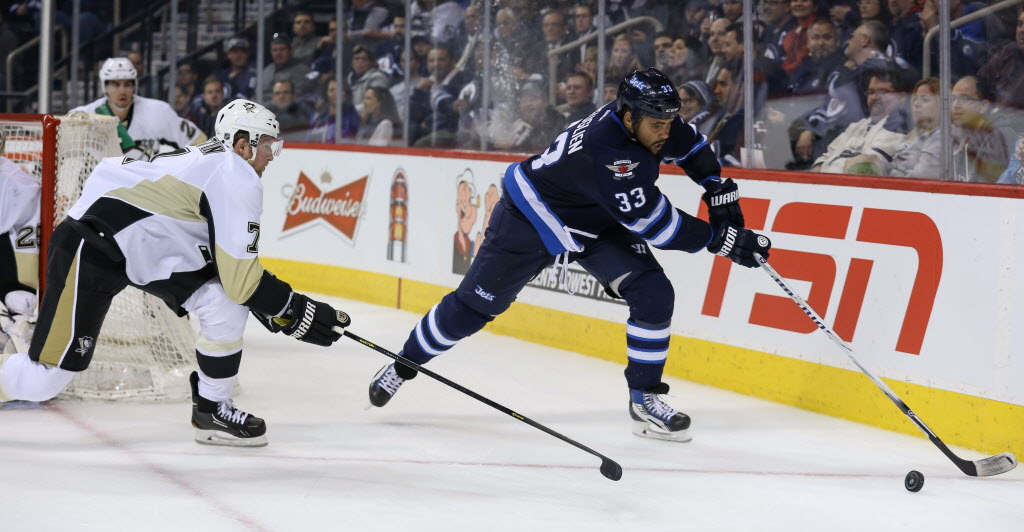 Dustin Byfuglien is chased down by Pittsburgh Penguin Paul Martin (7).