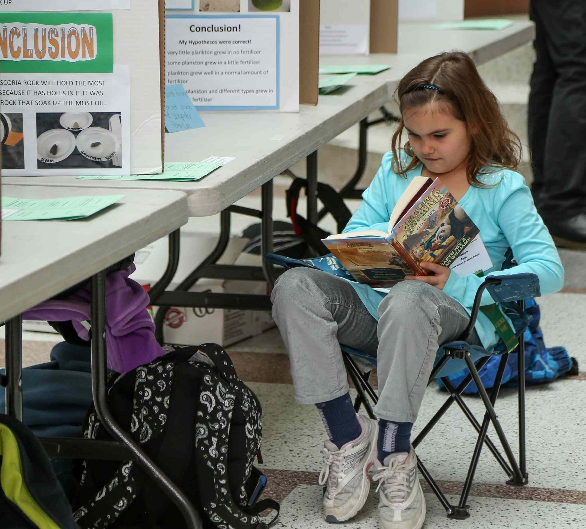 Shaelyn Eck, a Grade 4 student at Ecole Robert H. School, can't get enough learning in as she sits at her science fair display at the 44th Annual Winnipeg Schools' Science Fair at the University of Manitoba on Wednesday.