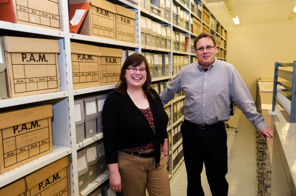 Kathleen Epp and Scott Goodine stand in the vault of the Manitoba archives.