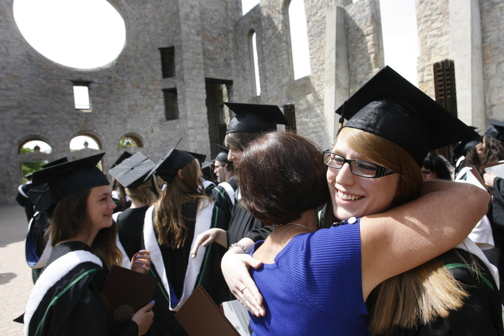 At right, Breanna Vandenberghe in the graduating class of  the Universite de Saint-Boniface students is congratulated after she received her Bachelor of Education degree at the University of Manitoba Convocation held in the Saint Boniface Cathedral Monday. (Wayne Glowacki / Winnipeg Free Press)