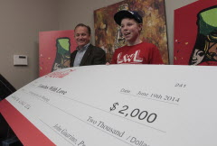 Lunches With Love founder Nathan Unrau accepts a cheque from Coca-Cola Refreshments Canada president John Guarino Thursday.