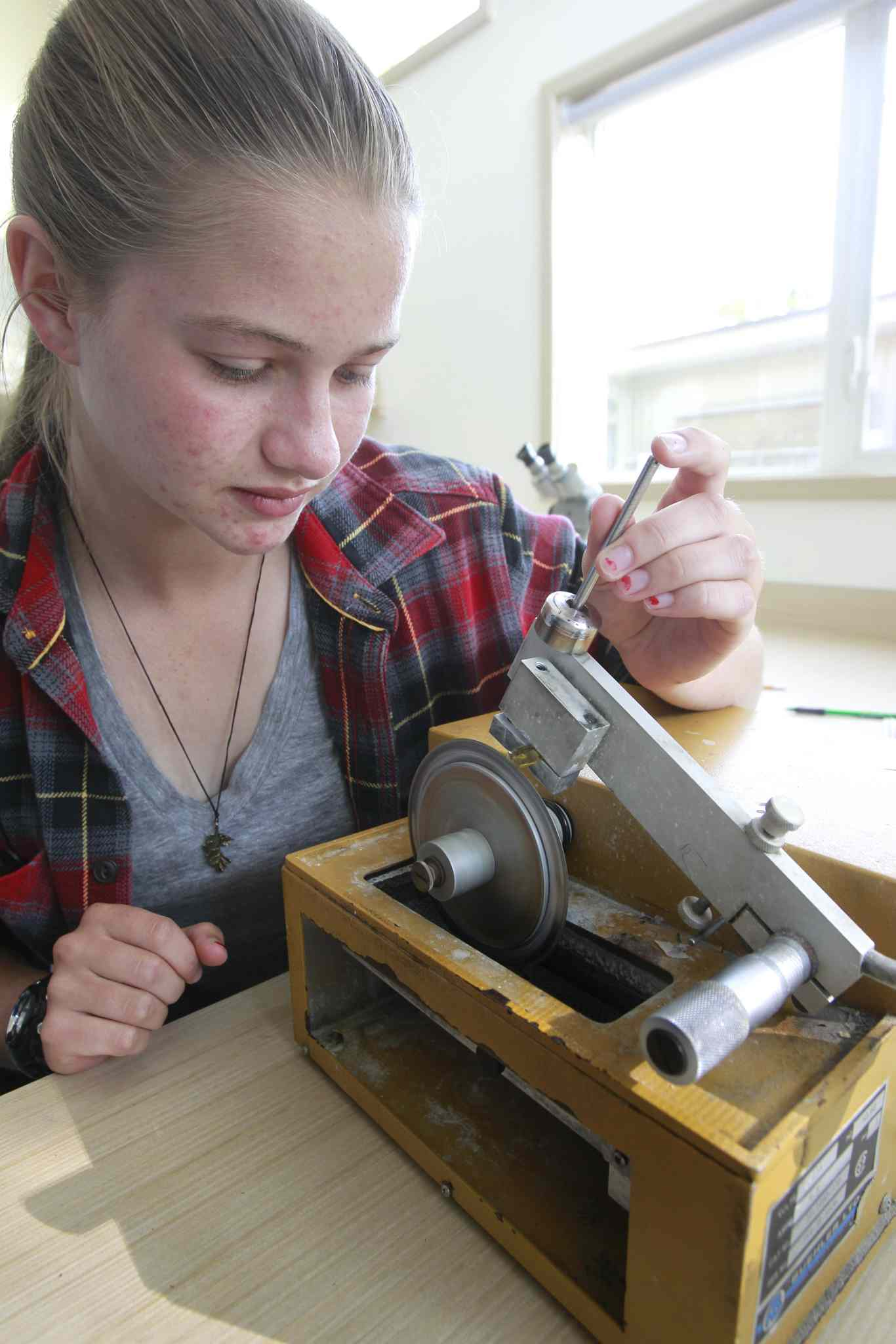 In the field station, Hanna Bohm uses a low-speed saw to cut a slice of a pike specimen to view under a microscope.