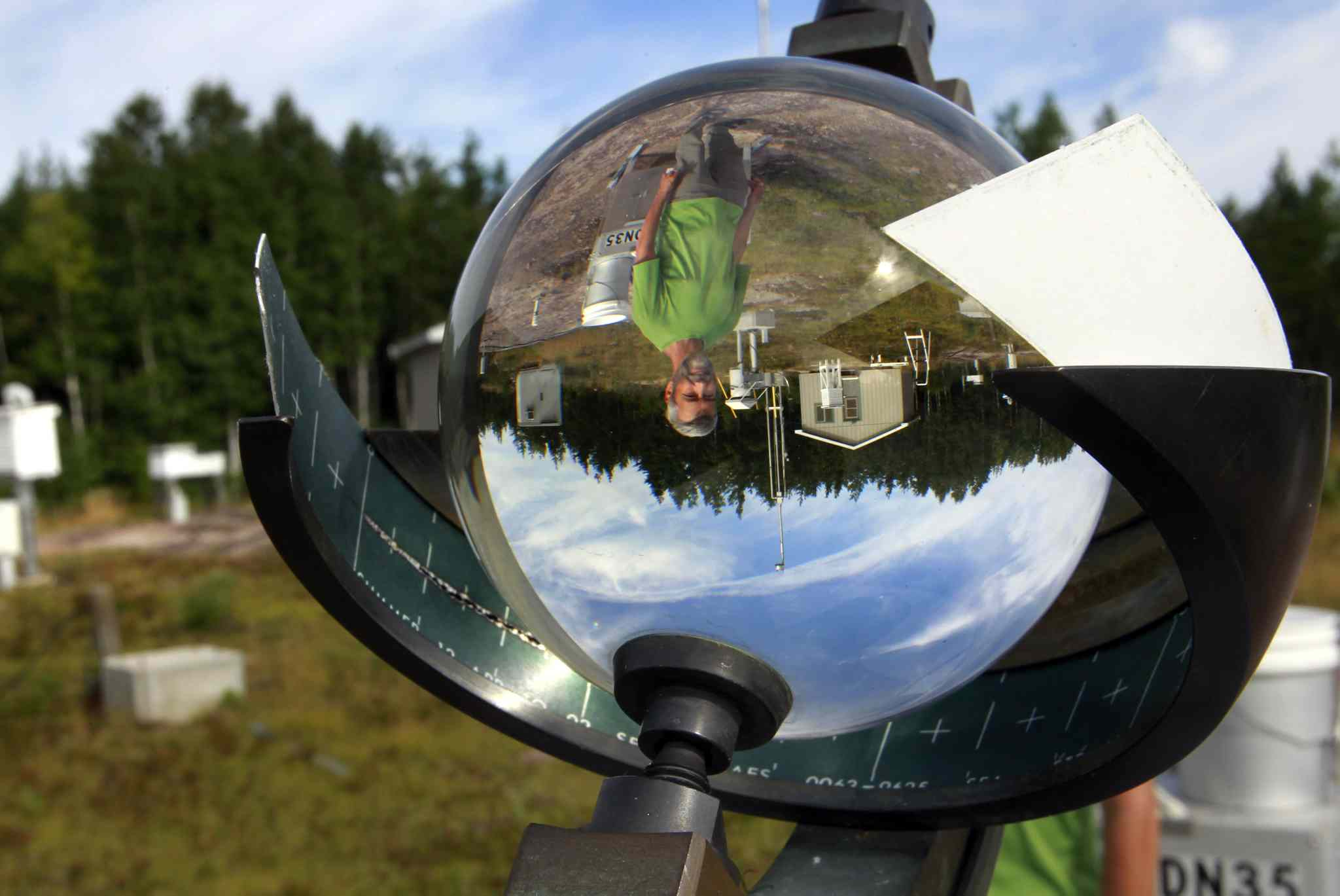 Near the Field Station, Dean McLeod is reflected in the glass sphere of a Campbell-Stokes Sunshine Recorder, one of the many instruments at the Experimental Lakes Area Meteorological and Atmospheric Chemistry Monitoring Site established in 1969.