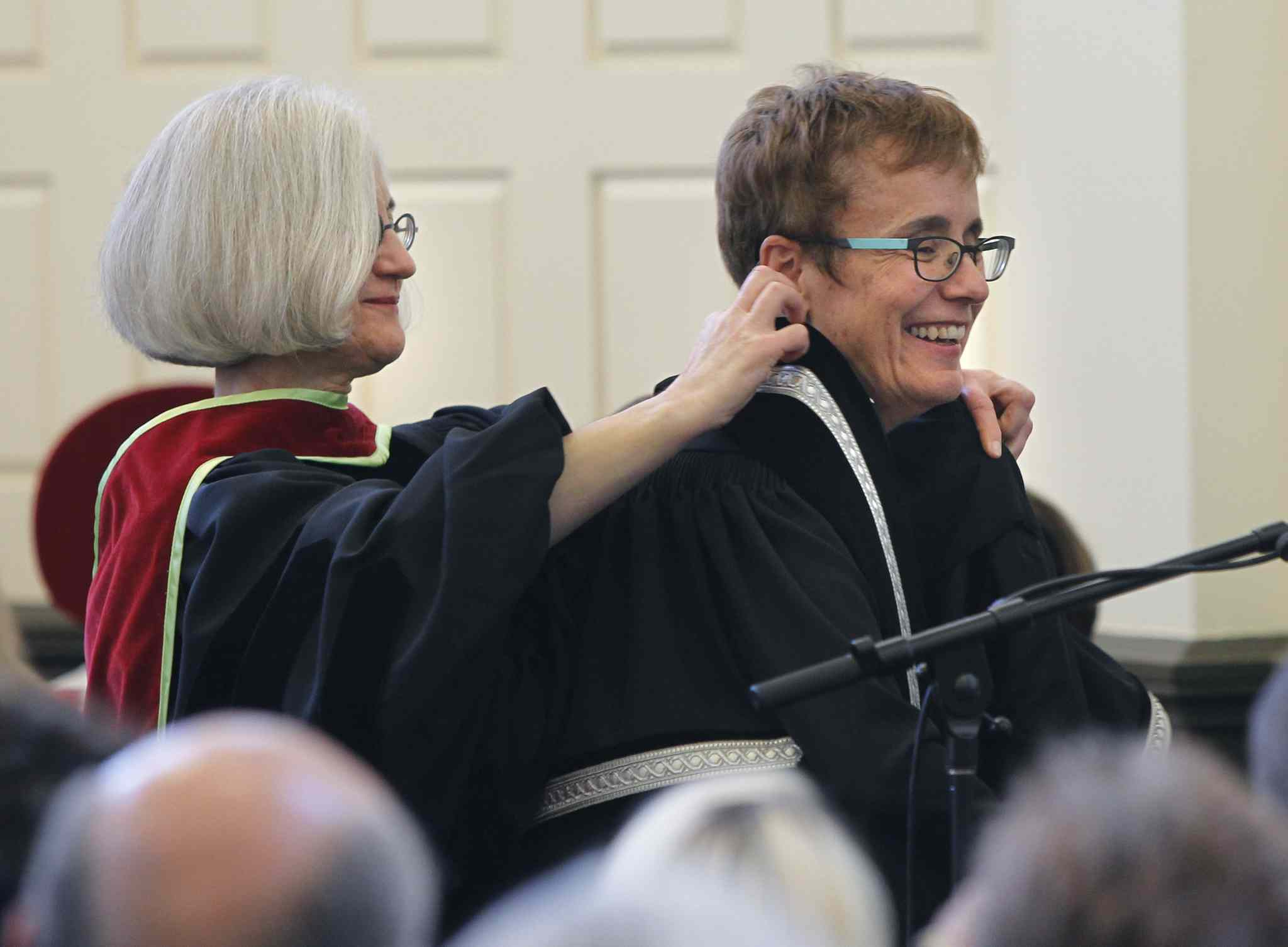 Wendy Josephson places the robe on Annette Trimbee, the new president of the University of Winnipeg, during an inauguration ceremony that featured dancers from the School of Contemporary Dance.