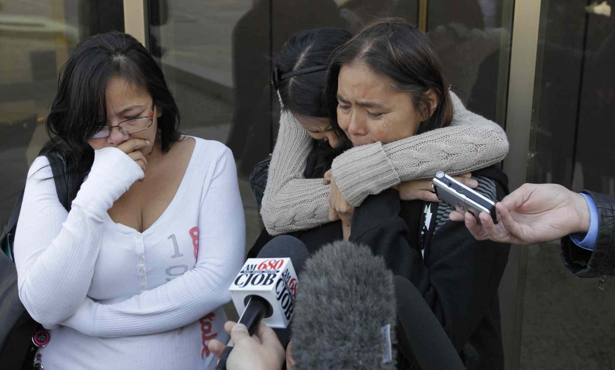 Members of Tina Fontaine's family speak to reporters following the sentencing hearing for the men who pleaded guilty to killing Tina's father, Eugene Fontaine, in 2011. At right, Eugene's sister Lana Fontaine is comforted by relatives outside court. The judge reserved sentencing Wednesday.