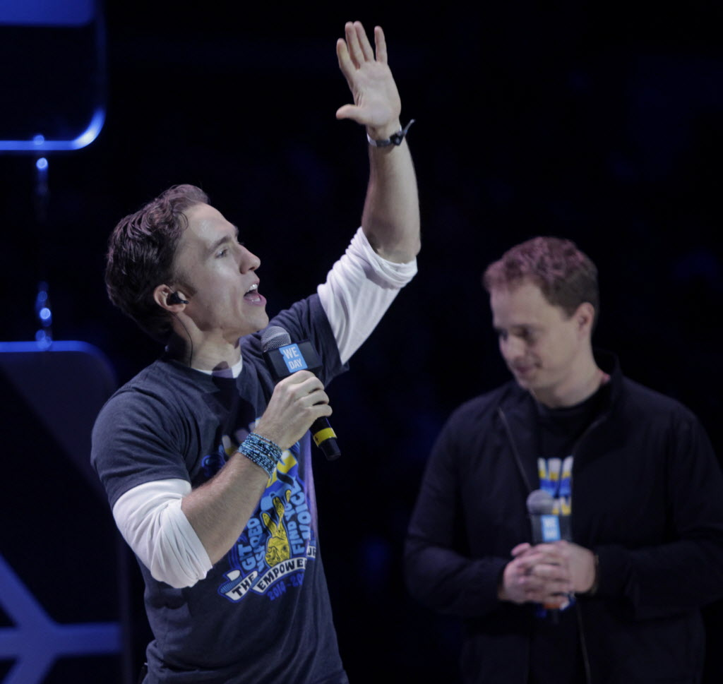 Craig (left) and Marc Kielburger near the end of the We Day event in the MTS Centre Wednesday. (Wayne Glowacki / Winnipeg Free Press )