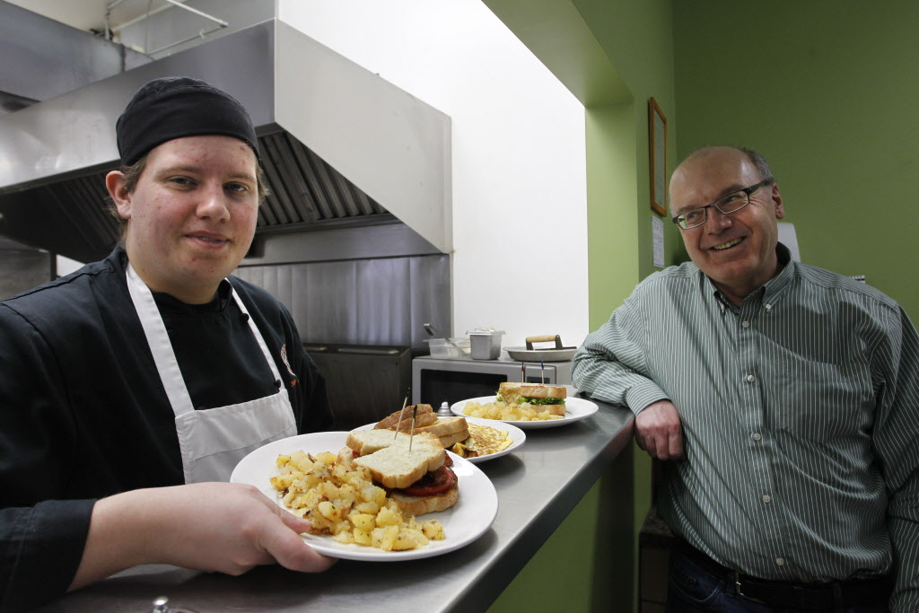 Nolan Saunders (left), with Jim Lapp, shows off meals prepared at L'Arche Tova Café.