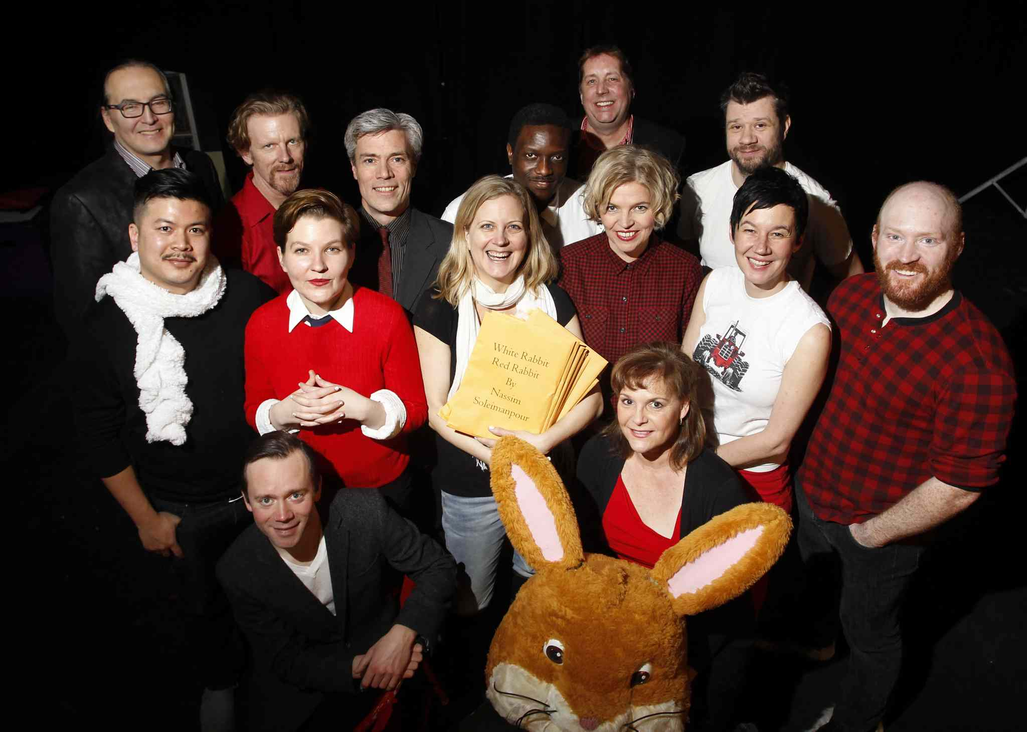 Theatre Projects Manitoba is staging White Rabbit, Red Rabbit.  Artistic director Ardith Boxall (centre) holding the scripts, while surrounded by some of the actors taking part in the production. From left to right in front are Tom Keenan and Janice Skene; second row: Loc Lu, Sarah Constible, Sharon Bajer, Shawna Dempsey and Carson Nattress; back row: Ian Ross, Arne McPherson, Gord Tanner,  Bathelemy Bolivar, Leith Clark and  Stephen Sim. Every night a lone actor will be given the script they have never seen before and then perform it on the spot.