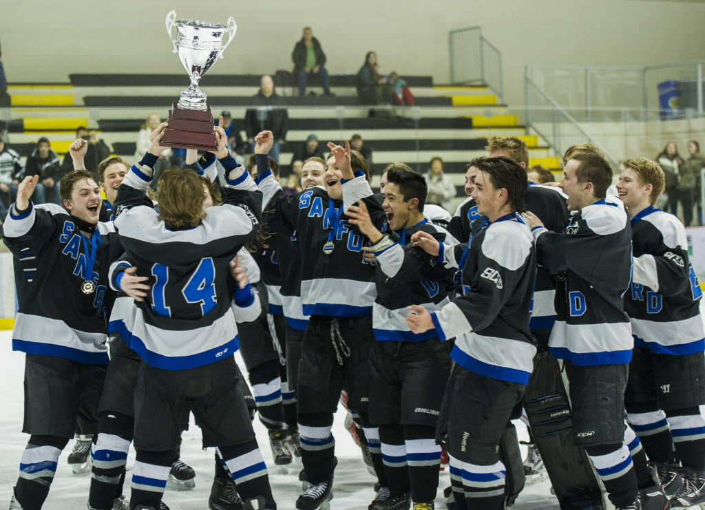 The Sanford Sabres hoist the cup and cheer as they celebrate their win over the Lord Selkirk Royals. (DAVID LIPNOWSKI / WINNIPEG FREE PRESS)