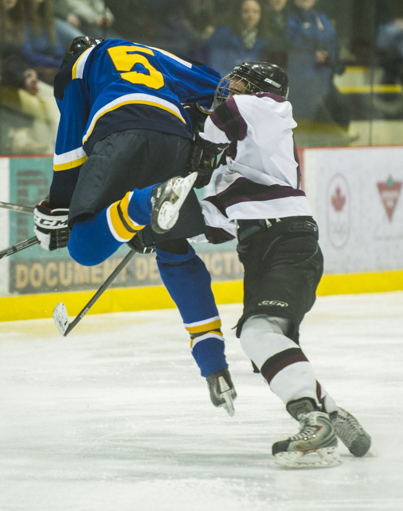 Warren Wildcats Josh Hofer (#5) jumps up against a Springfield Sabres player during their Winnipeg High School Hockey League game.
