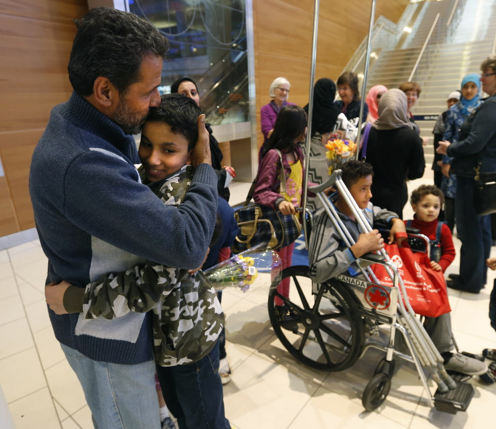 Young Mohammed Abdullah hugs his uncle Kamal who was one of the 24 Syrians that arrived at Richardson International Airport this afternoon. At right in the wheelchair is Mohammed's cousin Omar,14.