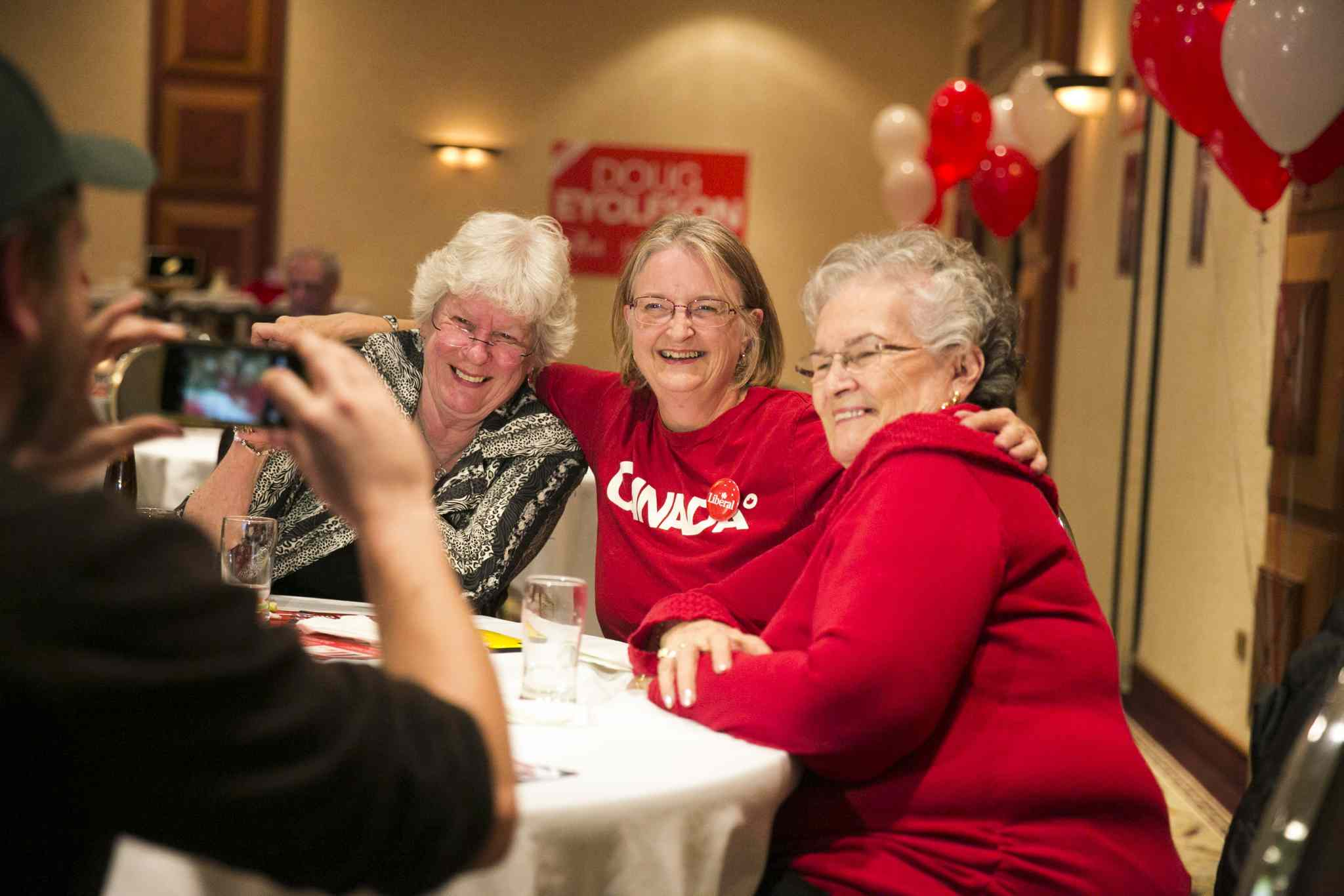 Liberal supporters Barb King (left), Margaret Semple, and Jeannette Metcalfe a celebrate Doug Eyolfson's win at a Holiday Inn in Winnipeg on Monday, Oct. 19, 2015.