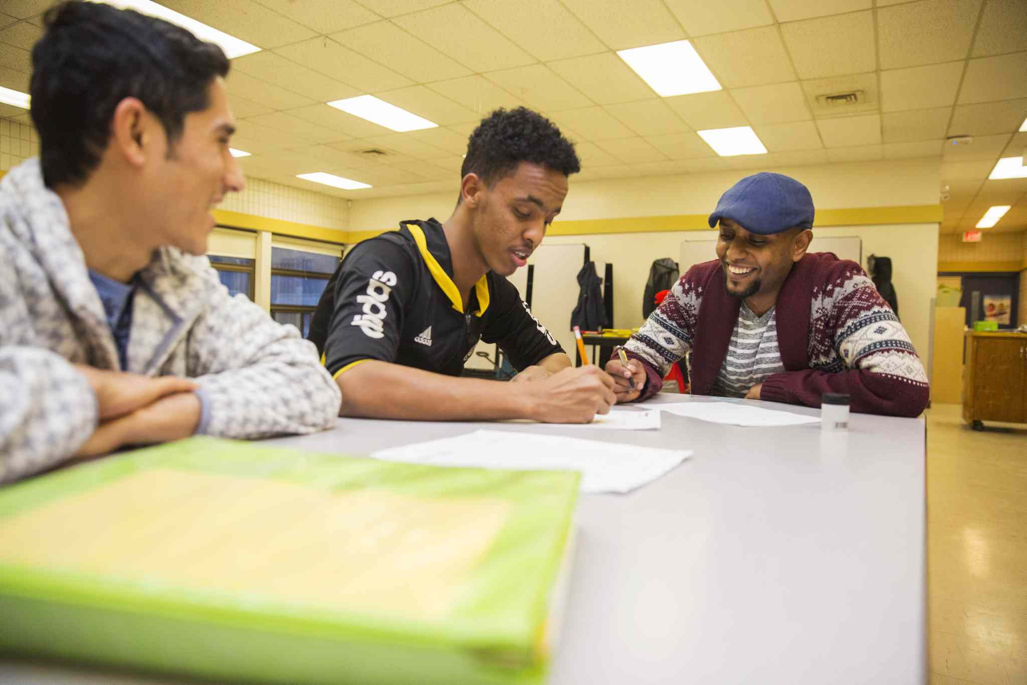 Surafel Kuchem works with volunteer Shakaib Hassani, far left, and student Salman Hassan, centre, at the Homework and Education for Youth (HEY) program at Victoria-Albert School in Winnipeg.