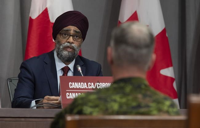 Chief of Defence Staff Jonathan Vance, right, looks on as National Defence Minister Harjit Sajjan makes his opening remarks at a news conference in Ottawa, Friday, June 26, 2020. Sajjan is dismissing suggestions the federal government is planning to take an axe to military spending as it seeks to keep the federal deficit under control during COVID-19. THE CANADIAN PRESS/Adrian Wyld