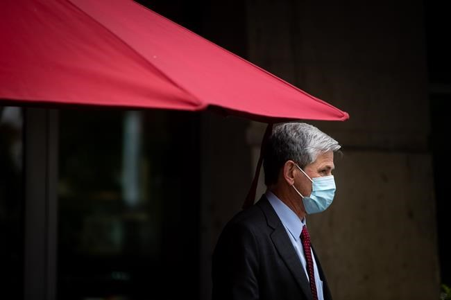 Liberal Leader Andrew Wilkinson stands under a patio umbrella during a campaign stop at a cafe, in Coquitlam, B.C., on Thursday, October 15, 2020. The B.C. Liberals announced Thursday that Laurie Throness was not representing the party in Chilliwack-Kent after making comments at an all-candidates meeting comparing free birth control to eugenics. THE CANADIAN PRESS/Darryl Dyck