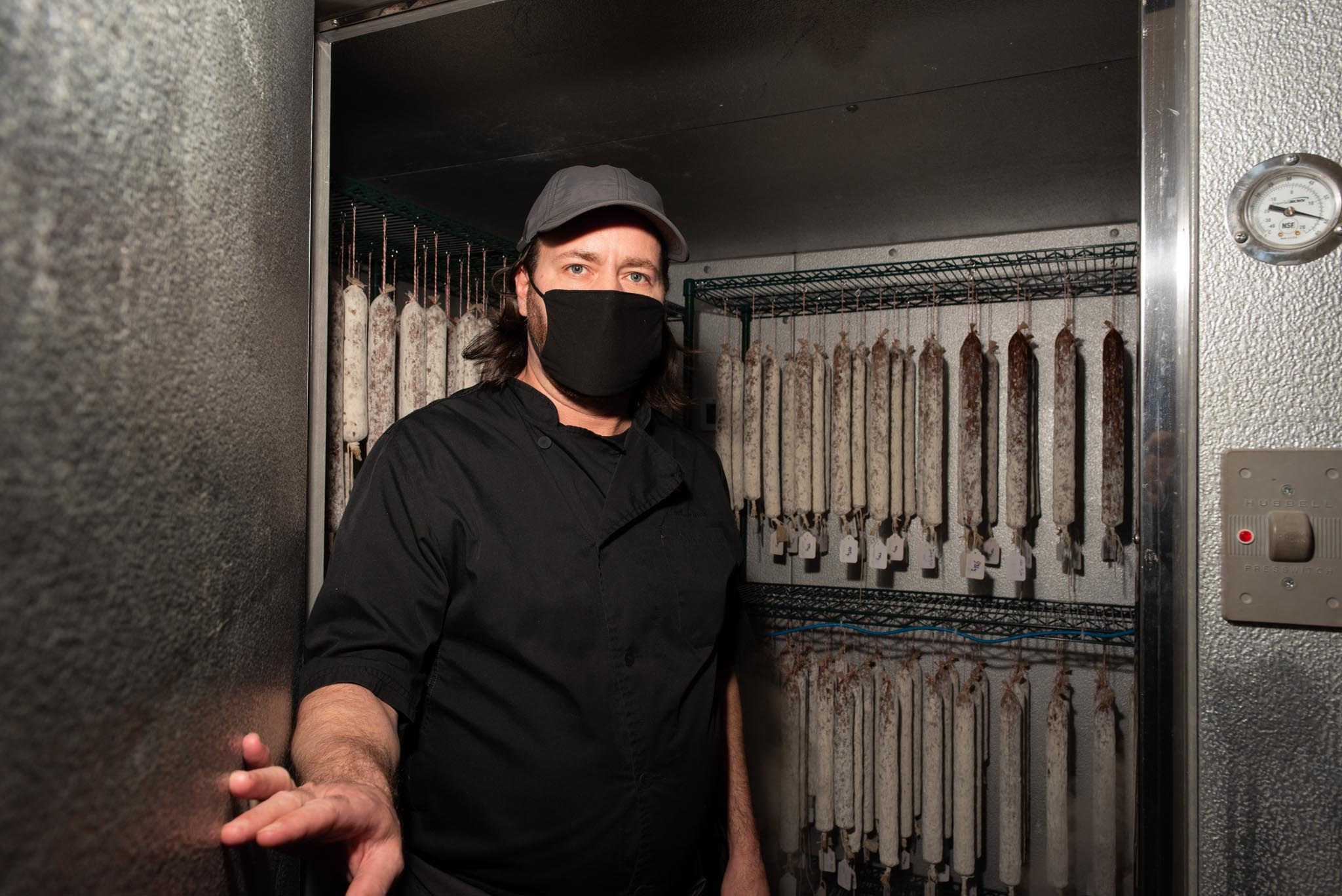Chef and owner Tristan Foucault shows off the charcuterie walk-in cooler for their house-made cured meats.
