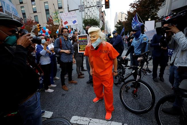 A demonstrator dressed in a prison suit and wearing a mask to resemble President Donald Trump stands outside the Pennsylvania Convention Center where votes are being counted, Friday, Nov. 6, 2020, in Philadelphia. THE CANADIAN PRESS/AP-Rebecca Blackwell