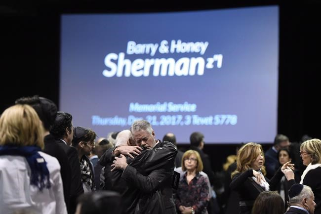 People embrace before the start a memorial service for Apotex billionaire couple Barry and Honey Sherman in Mississauga, Ontario on Thursday, December 21, 2017.Toronto police say they have identified a person of interest in the high-profile 2017 homicides of a billionaire philanthropist couple. THE CANADIAN PRESS/Nathan Denette