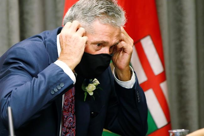Manitoba Premier Brian Pallister puts on a mask after speaking to media before the throne speech at the legislature in Winnipeg on Wednesday, Oct. 7, 2020. The government is offering to help restaurants pay for delivery costs during the COVID-19 pandemic. THE CANADIAN PRESS/John Woods