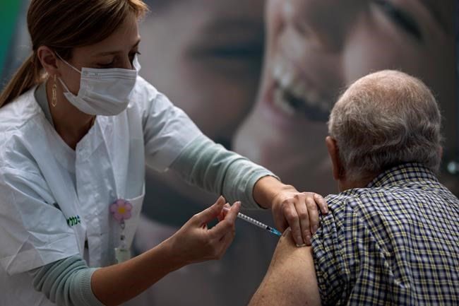 A man receives a COVID-19 vaccine from medical staff at a COVID-19 vaccination center in Tel Aviv, Israel, Wednesday Jan. 6, 2021. THE CANADIAN PRESS/AP/Oded Balilty