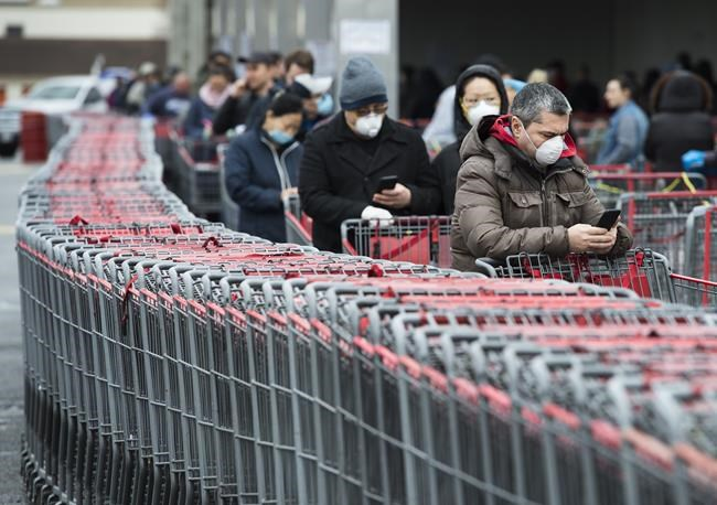 People wait in line to enter a Costco store in Toronto on Monday, April 13, 2020. Canadians who weren't happy with some of their holiday gifts or who changed their mind after making purchases might face trouble when trying to get their money back. THE CANADIAN PRESS/Nathan Denette