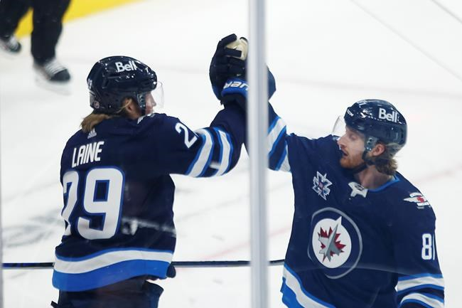 Winnipeg Jets' Patrik Laine (29) and Kyle Connor (81) celebrate Laine's goal during opening game first period NHL action against the Calgary Flames, in Winnipeg, Thursday. (John Woods / The Canadian Press)