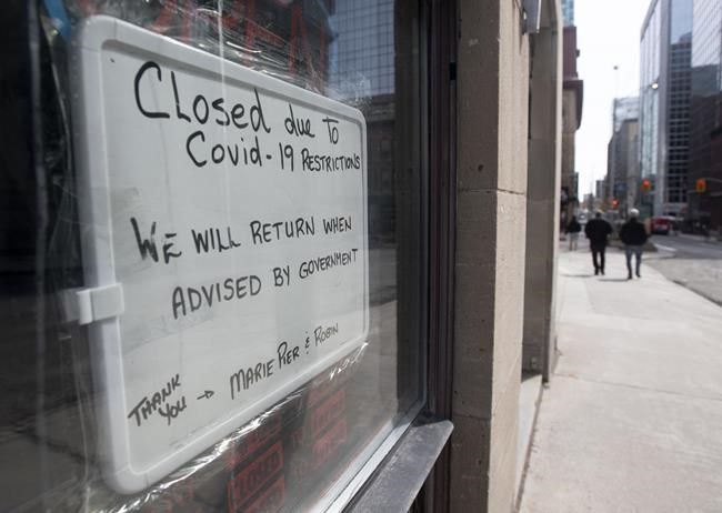 A sign in a barber shop window indicates the establishment is closed because of the COVID-19 virus in Ottawa on March 18, 2020. THE CANADIAN PRESS/Adrian Wyld