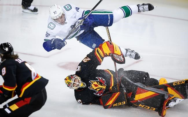 Vancouver Canucks' Tanner Pearson crashes over Calgary Flames goalie Jacob Markstrom during second-period NHL hockey action in Calgary, Wednesday, Feb. 17, 2021.THE CANADIAN PRESS/Jeff McIntosh