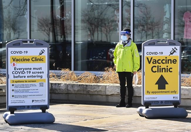A worker waits to assist people outside at a mass COVID-19 vaccination site during the COVID-19 pandemic in Mississauga, Ont., on Monday, March 22, 2021. THE CANADIAN PRESS/Nathan Denette