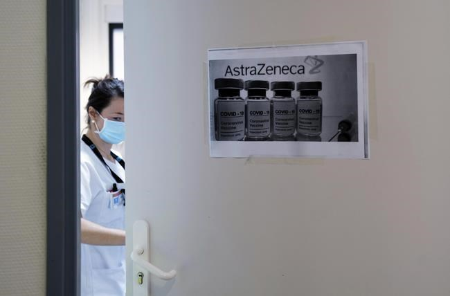 A health worker closes a door as she prepares doses of the AstraZeneca/Oxford vaccine at the Edouard Herriot hospital, Saturday, Feb. 6, 2021 in Lyon, central France. THE CANADIAN PRESS/Pool via AP-Olivier Chassignole