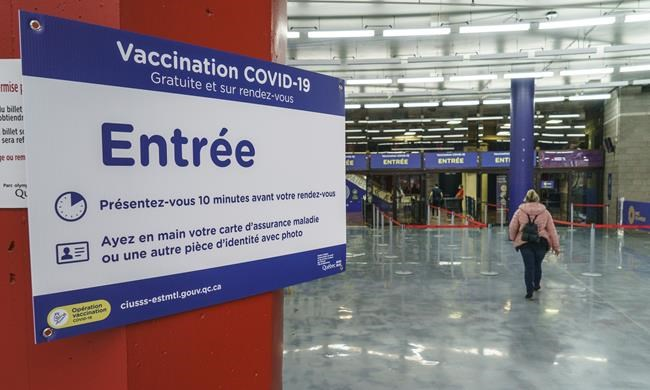 A lone person enters the COVID-19 vaccination clinic at Montreal's Olympic Stadium, on Wednesday, March 31, 2021. THE CANADIAN PRESS/Paul Chiasson