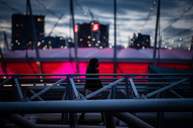 A person wearing a face mask to curb the spread of COVID-19 is silhouetted against B.C. Place stadium while walking over a pedestrian bridge on False Creek, in Vancouver, on Friday, April 2, 2021. THE CANADIAN PRESS/Darryl Dyck