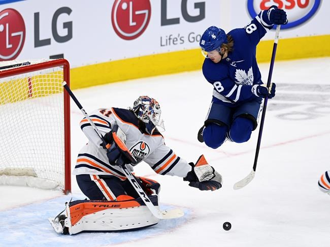 Toronto Maple Leafs centre William Nylander (88) jumps as he watches the puck as Edmonton Oilers goaltender Mike Smith (41) makes a save during first period NHL hockey action in Toronto on Monday March 29, 2021. Nylander will not play against the Montreal Canadiens tonight after having exposure with a possible positive case of COVID-19. THE CANADIAN PRESS/Frank Gunn