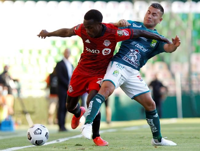 Richie Laryea of Canada's Toronto FC, left, and Jean Meneses of Mexico's Leon battle for the ball during a Concacaf Champions League soccer match in Leon, Mexico, Wednesday, April 7, 2021. (AP Photo/Mario Armas)