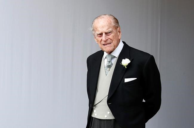 In this Friday, Oct. 12, 2018 file photo, Britain's Prince Philip waits for the bridal procession following the wedding of Princess Eugenie of York and Jack Brooksbank at St George's Chapel in Windsor Castle, England. Buckingham Palace officials say Prince Philip, the husband of Queen Elizabeth II, has died, it was announced on Friday, April 9, 2021. THE CANADIAN PRESS/AP/Alastair Grant