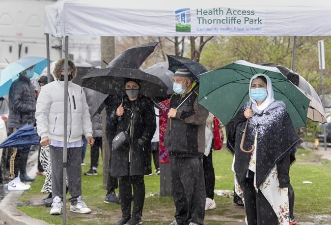 People line up in the rain for a COVID-19 vaccine at a pop-up clinic at the Masjid Darus Salaam in the Thorncliffe Park neighbourhood in Toronto on Sunday, April 11, 2021. Thousands of people have lined up over the weekend for vaccine doses at the mosque in the hard hit neighbourhood. THE CANADIAN PRESS/Frank Gunn