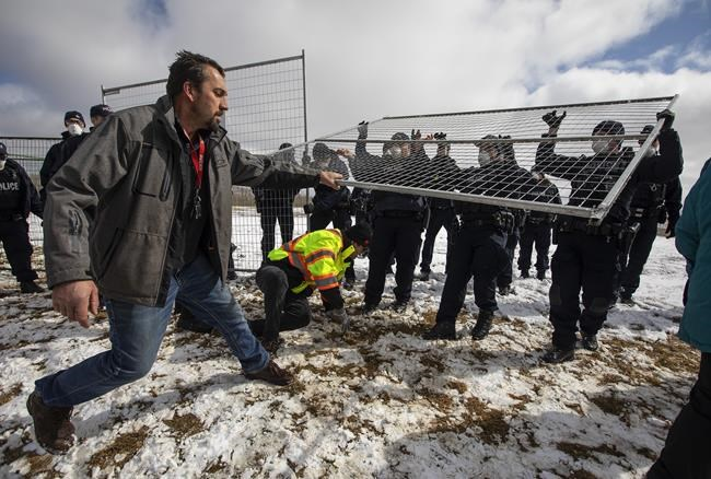 Supporters try to tear down the fence as police struggle with them outside GraceLife Church near Edmonton, Alta., on Sunday, April 11, 2021. The church has been fenced off by police and Alberta Health Services in violation of COVID-19 rules. THE CANADIAN PRESS/Jason Franson