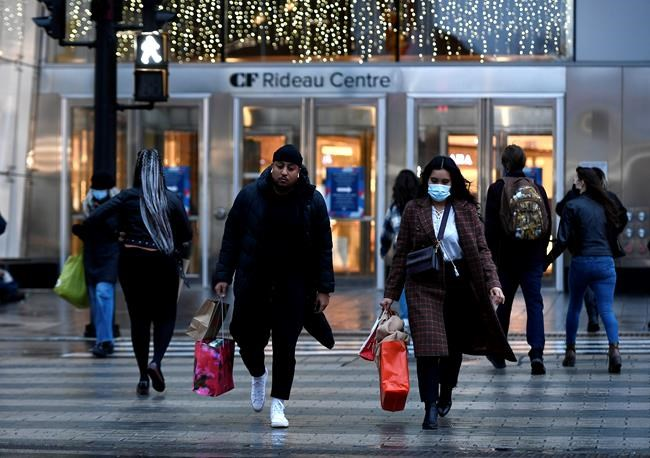 People leave after shopping at a mall in Ottawa, on Christmas Eve, Thursday, Dec. 24, 2020. THE CANADIAN PRESS/Justin Tang