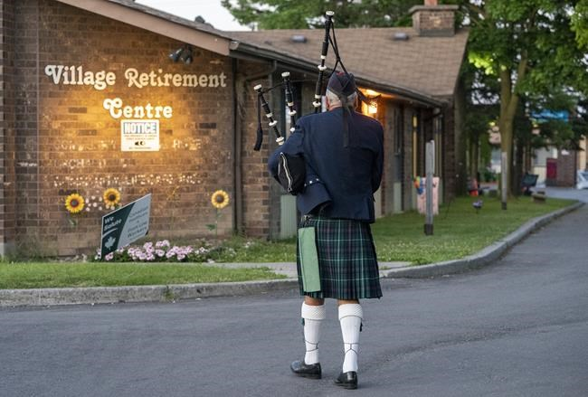 The federal budget is promising billions to close gaps in long-term care and Canada's vaccine production laid bare by the COVID-19 pandemic. A piper marches off during a vigil for COVID-19 victims at the Orchard Villa long-term care home in Pickering, Ont. on Monday June 15, 2020. THE CANADIAN PRESS/Frank Gunn