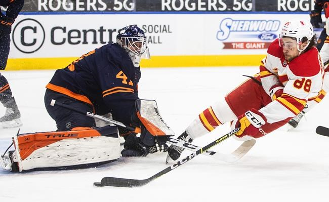 Edmonton Oilers goalie Mike Smith (41) makes the save on Calgary Flames' Andrew Mangiapane (88) during first-period NHL action in Edmonton on Thursday, April 29, 2021.THE CANADIAN PRESS/Jason Franson