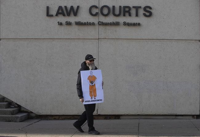A supporter stands outside court in Edmonton on Thursday, March 4, 2021, as Pastor James Coates of GraceLife Church appears in court to appeal bail conditions. He was arrested for allegedly holding Sunday services in violation of COVID-19 rules. A trial is to begin Monday. THE CANADIAN PRESS/Jason Franson
