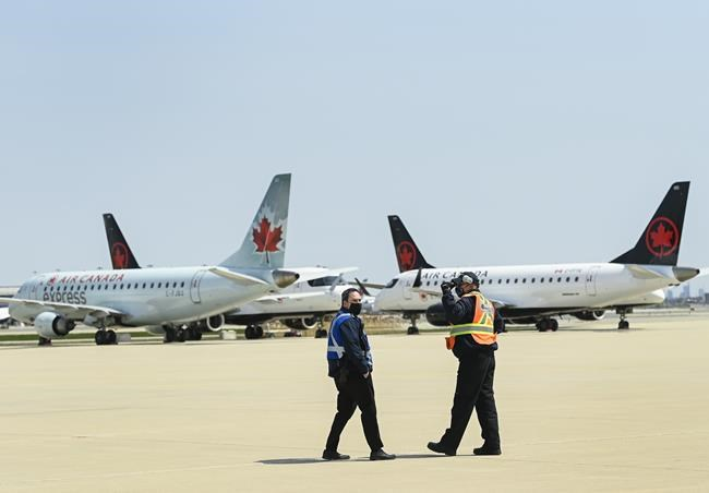 Airline groundcrew walks past grounded Air Canada planes as they sit on the tarmac at Pearson International Airport during the during the COVID-19 pandemic in Toronto on Tuesday, April 27, 2021. THE CANADIAN PRESS/Nathan Denette