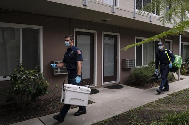 Torrance firefighter Trevor Borello, left, carries a cooler containing the Pfizer COVID-19 vaccine as he walks to an apartment to inoculate two sisters suffering from muscular dystrophy, Wednesday, May 12, 2021, in Torrance, Calif. Teamed up with the Torrance Fire Department, Torrance Memorial Medical Center started inoculating people at home in March, identifying people through a city hotline, county health department, senior centers and doctor's offices, said Mei Tsai, the pharmacist who coordinates the program. (AP Photo/Jae C. Hong)