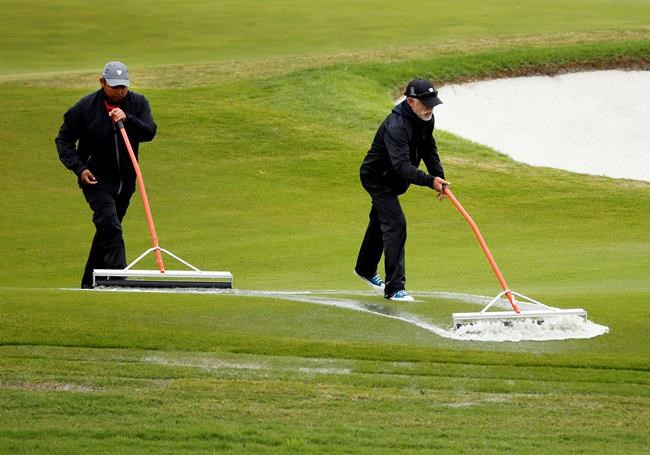 Course works squeegee the apron of the 18th green following an over two hour delay during the final round of the AT&T Byron Nelson golf tournament in McKinney, Texas, Sunday, May 16, 2021. (AP Photo/Ray Carlin)