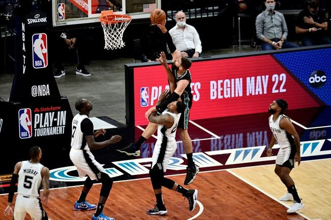 Memphis Grizzlies center Jonas Valanciunas (17) shoots over San Antonio Spurs forward Rudy Gay (22) during the first half of an NBA basketball Western Conference play-in game Wednesday, May 19, 2021, in Memphis, Tenn. (AP Photo/Brandon Dill)