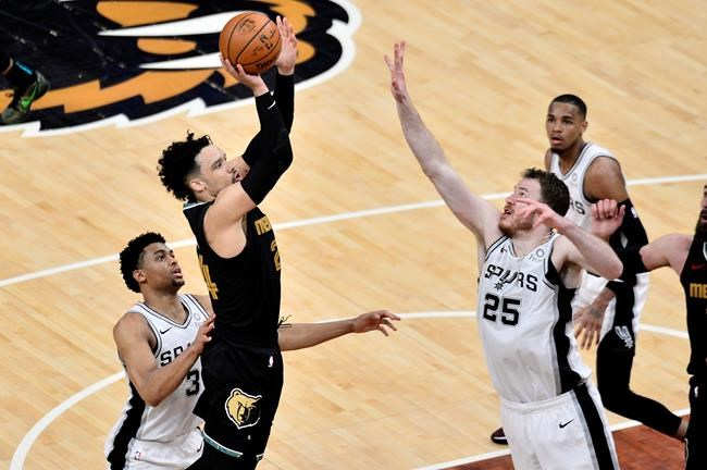 Memphis Grizzlies forward Dillon Brooks (24) shoots against San Antonio Spurs center Jakob Poeltl (25) and forward Keldon Johnson (3) during the second half of an NBA basketball Western Conference play-in game Wednesday, May 19, 2021, in Memphis, Tenn. (AP Photo/Brandon Dill)