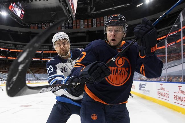 Edmonton Oilers' Slater Koekkoek (20) and Winnipeg Jets' Trevor Lewis (23) battle for the puck during first period NHL Stanley Cup playoff action in Edmonton on Friday, May 21, 2021.THE CANADIAN PRESS/Jason Franson