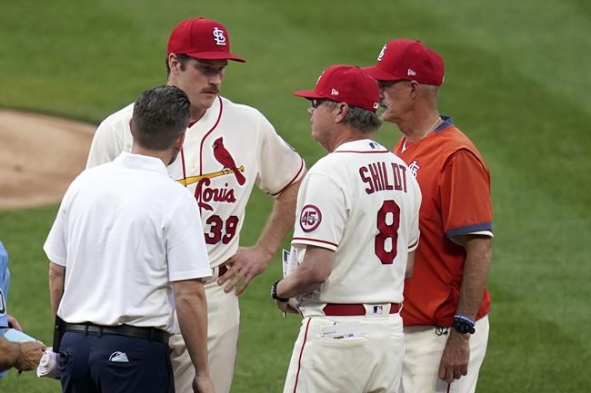 St. Louis Cardinals starting pitcher Miles Mikolas (39) talks with manager Mike Shildt (8) as pitching coach Mike Maddux, right, and trainer Adam Olsen, left, listen before the start of the fifth inning of a baseball game against the Chicago Cubs Saturday, May 22, 2021, in St. Louis. Mikolas walked off the field before warming up for the inning. (AP Photo/Jeff Roberson)