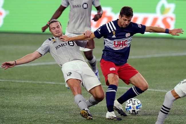 Montreal Impact's Samuel Piette, left, grapples with New England Revolution's Matthew Polster, right, during the second half of an MLS soccer match, Wednesday, Sept. 23, 2020, in Foxborough, Mass. THE CANADIAN PRESS/AP/Steven Senne