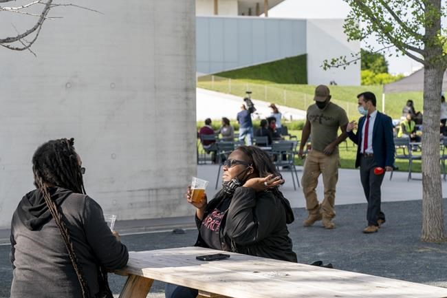 """In this May 6, 2021 photo, Semajh Daniels, left, and Zora McCarthy, both of Hyattsville, Md., enjoy a complimentary beer after receiving the J & J COVID-19 vaccine, at The REACH at the Kennedy Center in Washington. Free beer is the latest White House-backed incentive for Americans to get vaccinated for COVID-19. President Joe Biden is expected to announce a """"month of action"""" on Wednesday to get more shots into arms before the July 4 holiday. (AP Photo/Jacquelyn Martin)"""